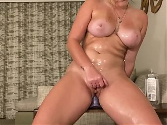 Sexy oiled up redhead fucks her ass with a dildo